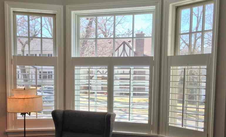 Half white shutters in living room bay window.