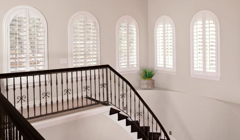 Plantation shutters on uniquely shaped windows.