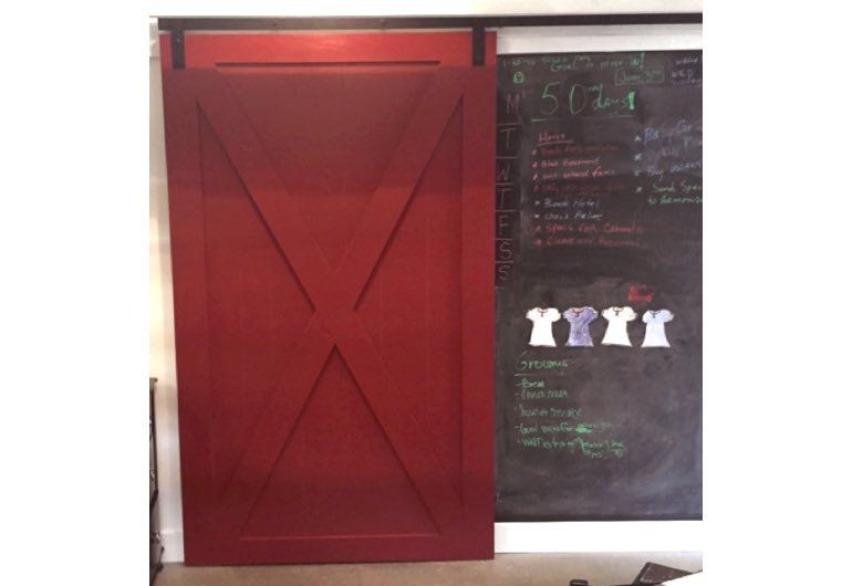 Bright red sliding barn door with black track next to chalkboard 🚪