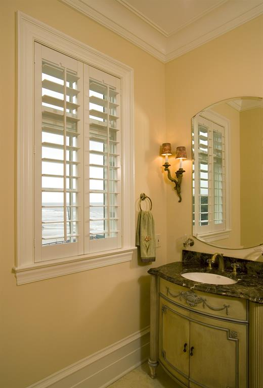 White plantation shutters in a light bathroom outlooking the ocean