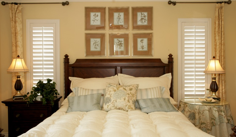 Bedroom with two tall plantation shutters on either side of bed in Minneapolis