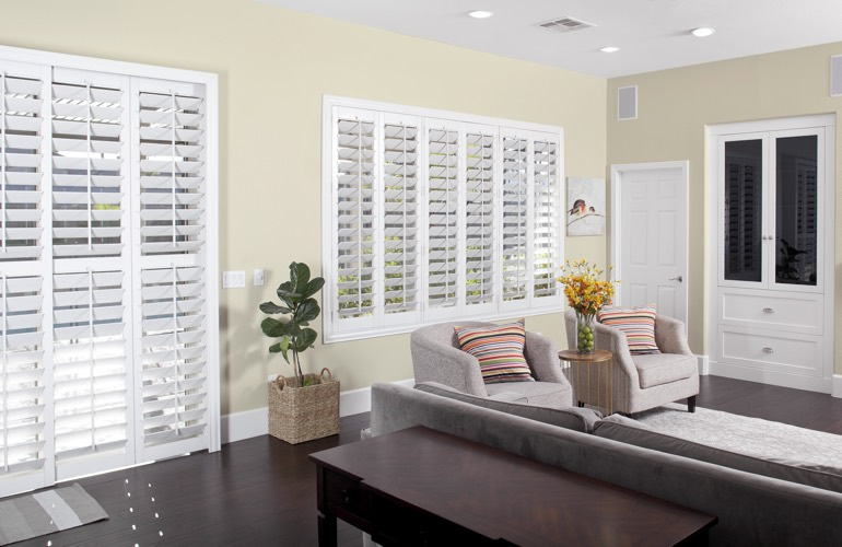 White plantation shutters in living room with dark wood floors